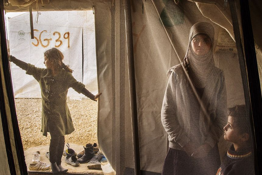 In this 2013 photograph (above) by Ed Kashi, a 13-year-old girl spends time with her siblings in her family tent at the Al Za'atri refugee camp for Syrians, near Mafraq, Jordan.