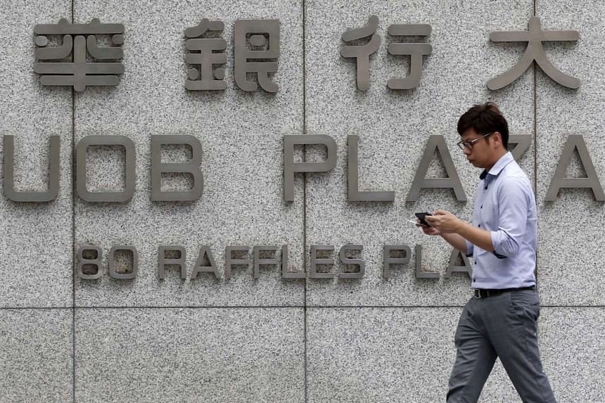 A man passes the United Overseas Bank Limited (UOB) offices in the central business district, on Jan 7, 2016.