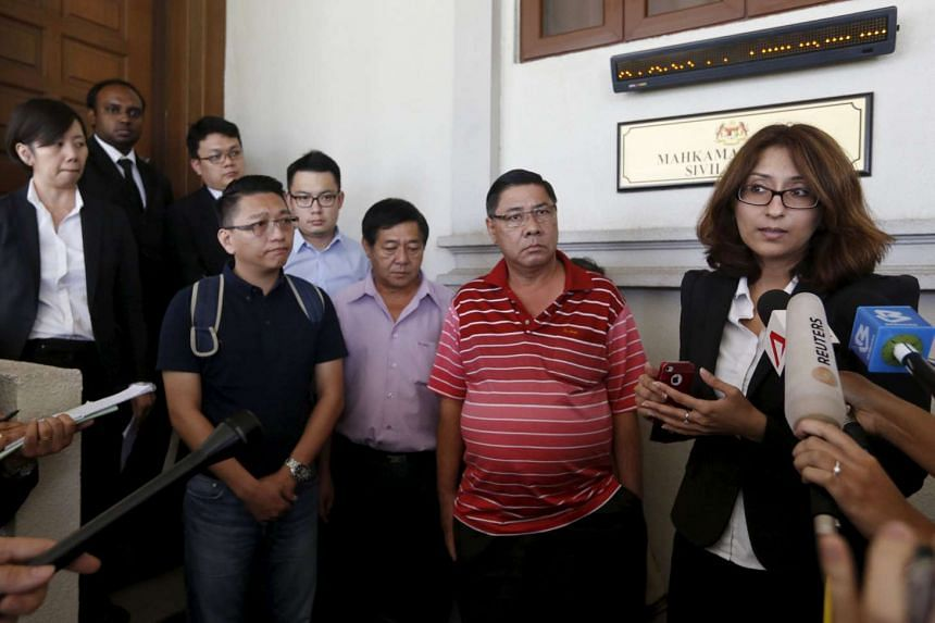 Relatives of MH370 passengers Tan Ah Meng, Chuang Hsiu Ling, and Tan Wei Chew during a hearing for the compensation suit brought against the Malaysian government and Malaysia Airlines over claims of negligence and breach of trust, in Kuala Lumpur on