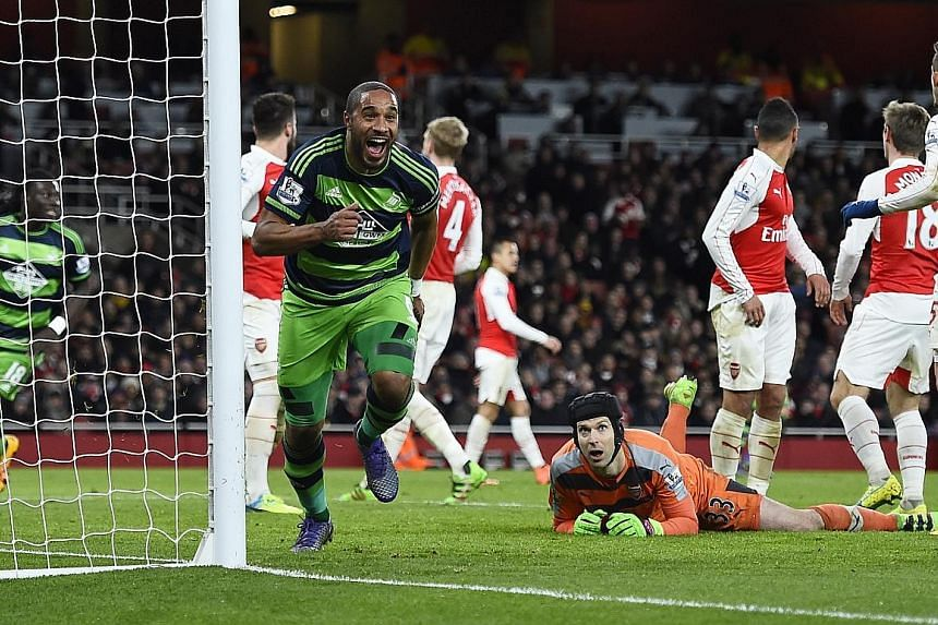 Swansea City defender Ashley Williams in jubilant mood after scoring the second goal against Arsenal as goalkeeper Petr Cech looks on. The 2-1 win puts Swansea six points clear of relegation and the Gunners have now lost three straight games in all c