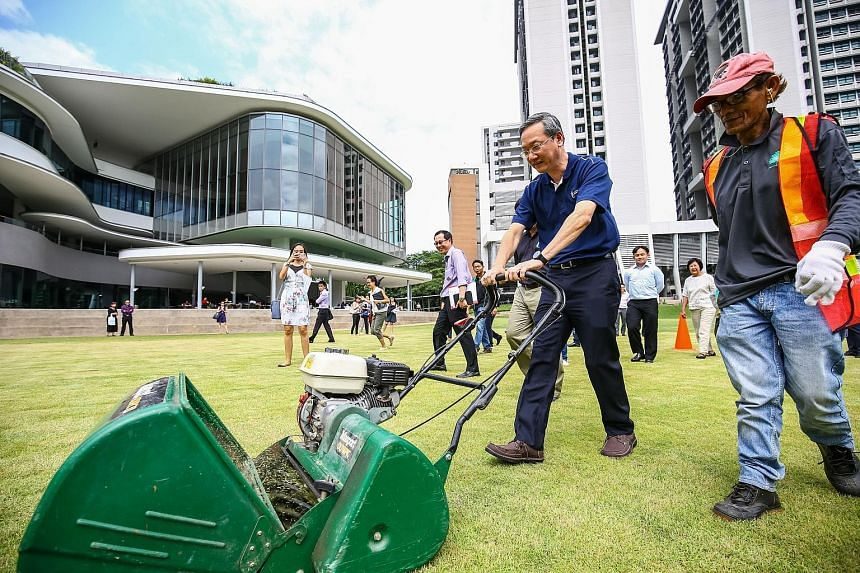 Mr Sam Tan trying out landscaping equipment at NUS University Town yesterday. He said employers can adopt a structured and targeted approach to provide more training and raise the skills of their workers.