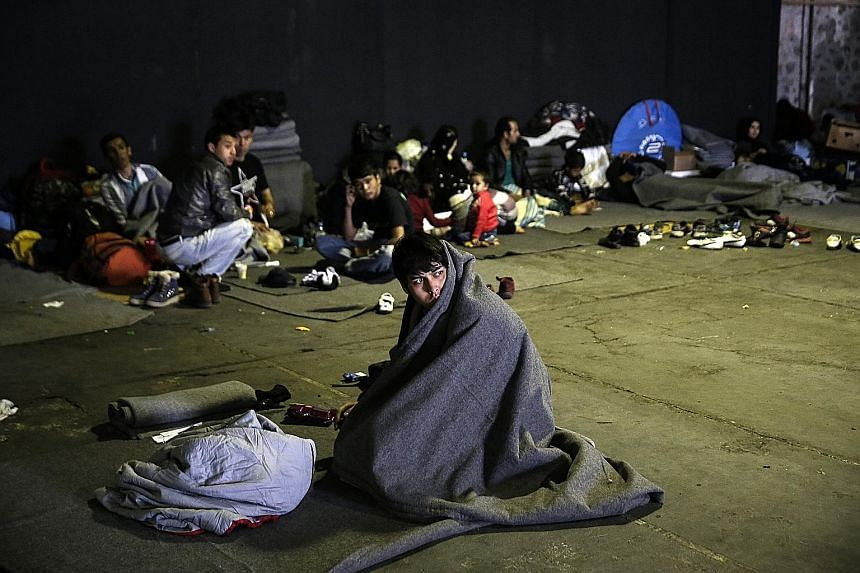 Refugees and migrants resting inside a warehouse used as a temporary shelter at the port of Piraeus, near Athens, on Wednesday.