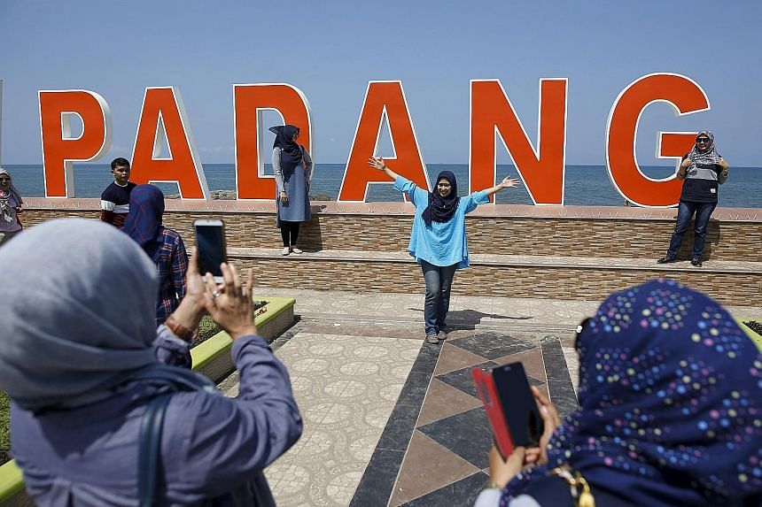 Visitors along the Sumatran coast posing for shots in front of the Indian Ocean yesterday, just a day after the magnitude 7.8 quake struck. It set off 11 aftershocks but, so far, there have been no reports of casualties or major damage.