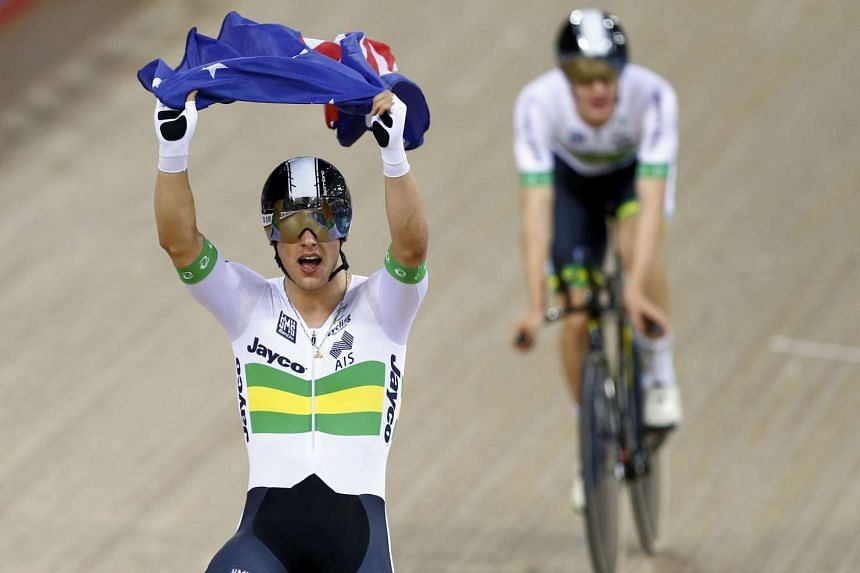 Sam Welsford of Australia celebrates with his national flag after winning gold.