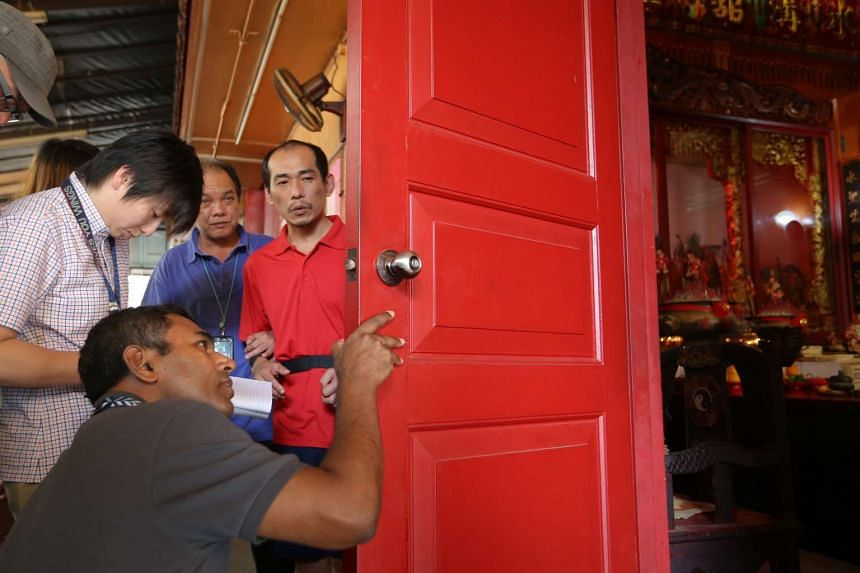 Loh Suan Lit (centre) looking on as investigators examine an area at Chin Long Kong Chinese Temple on March 2, 2016.