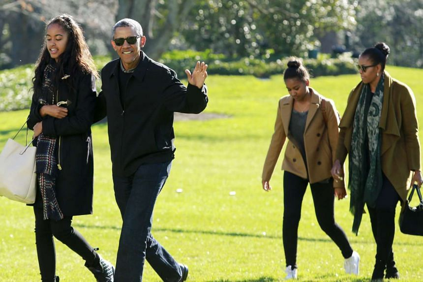 Obama waves as he walks with first lady Michelle (right) and their daughters Malia (left) and Sasha.