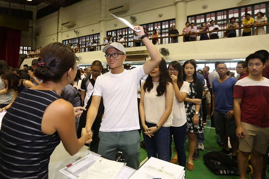 Mr Chua Chiah Soon (in white), 18, reacting after collecting his results.