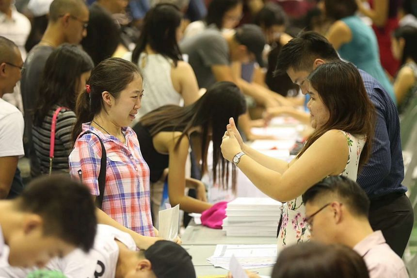 Civics tutor Mrs Violet Teo (right) giving a thumbs up to her student Ms Crystal Sia (left), 18, as she reacts after receiving her results.