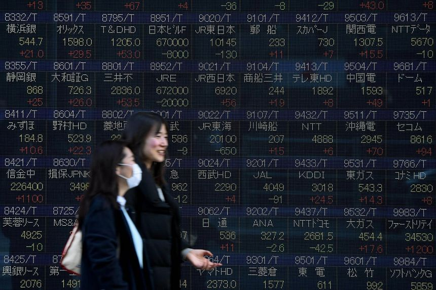 Women walk past an electric quotation board flashing share prices of the Tokyo Stock Exchange, on March 3, 2016.