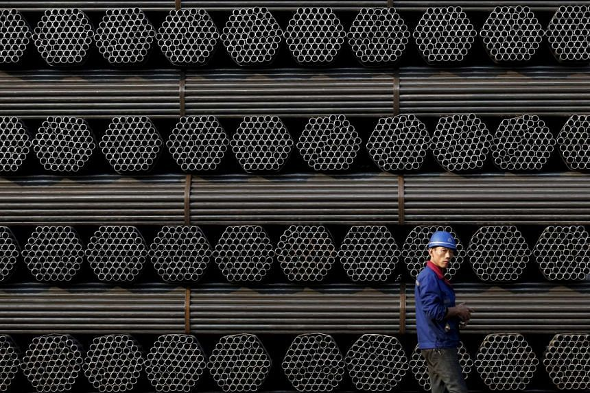 A worker walking past a pile of steel pipe products in China's Hebei province, on Nov 3, 2015.