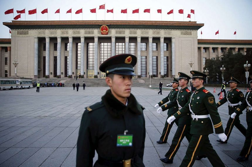 A soldier of the People's Liberation Army standing guard as paramilitary policemen march past in front of the Great Hall of the People ahead of the opening session of the National People's Congress in Beijing, China, on March 5, 2016.