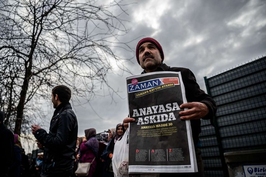 "A supporter of Turkish daily Zaman holding the latest edition of the newspaper on March 5, 2016. The headline says ""The Constitution is suspended""."