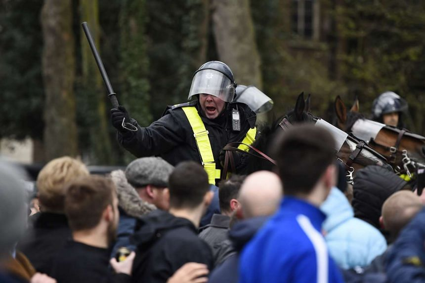 Policemen and fans clashing outside the ground before the match.
