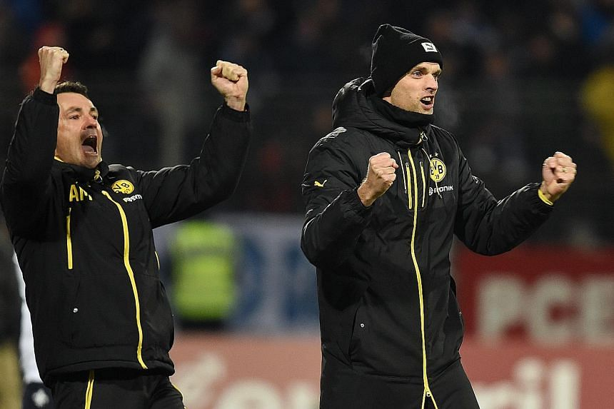 Borussia Dortmund manager Thomas Tuchel (right) celebrating with assistant Arno Michels during their 2-0 German Bundesliga win over Darmstadt on Wednesday. The result puts them five points behind league leaders Bayern Munich ahead of tonight's top-of