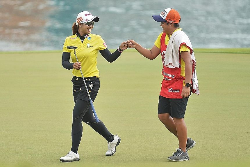Thai Pornanong Phatlum fist bumps her caddie after a good shot. She is tied for third alongside Norway's Suzann Pettersen and knows success will spark more interest in the game back home.