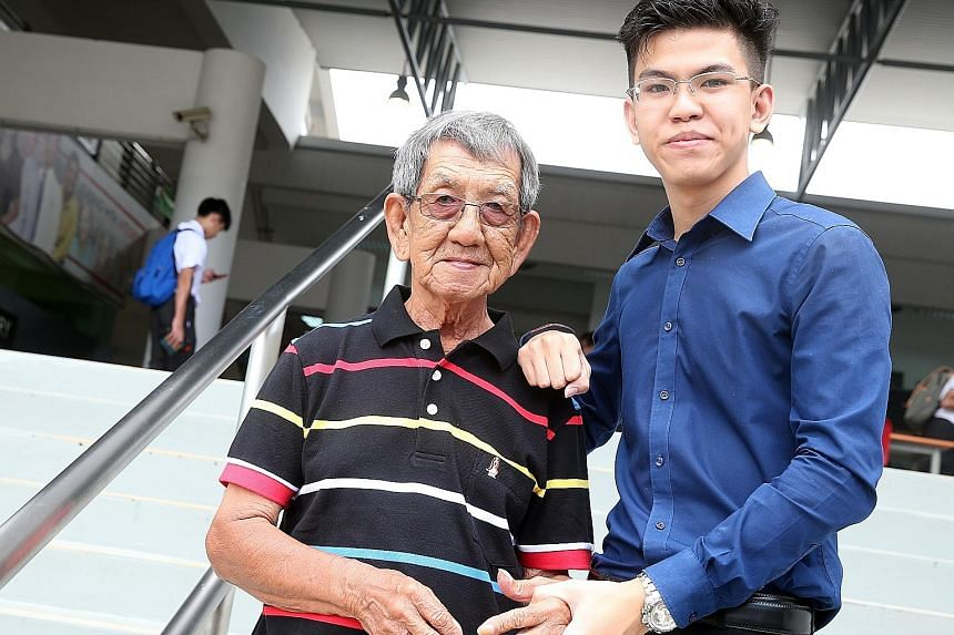 Richmond, 18, with his grandfather Tan Khoon Seng, 78, who holds a cleaning job and is the sole breadwinner of the family.