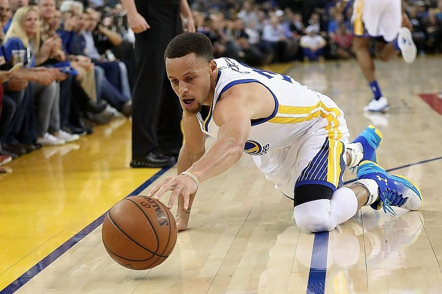 Golden State's Stephen Curry reaching for the ball during the game against Oklahoma City at the Oracle Arena. The Warriors defeated the Thunder 121-106.
