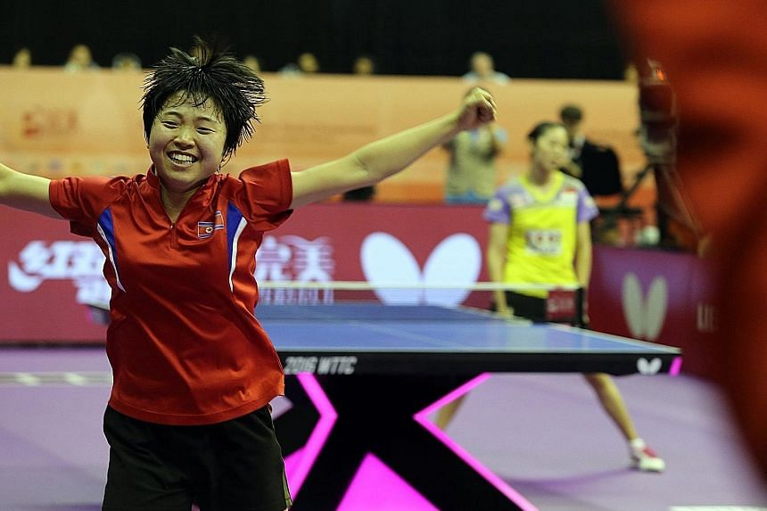 A shattered Yu Mengyu, who blamed herself for letting the team down, being consoled by an official (above) after her rubber-game loss to North Korea's Kim Song I (below) in the quarter-finals yesterday afternoon.