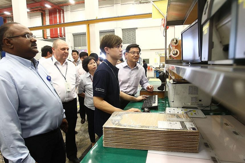 A worker at Pan Asia Logistics showing Mr Heng (right) how goods are being moved through a computerised process. Accompanying the minister are (from left) the firm's senior manager Sundaram Velosamy, executive chairman Christian Bischoff and chief ex
