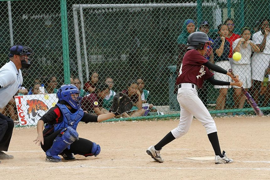 Chung Cheng High (Main) vice-captain and catcher Nicole Tay (in black) watches the play as Verryn Tan Li Ying, of 2014 champions Tanjong Katong Girls' School, swings at the pitch. Chung Cheng, beaten in the first round last year, won 7-1 yesterday to