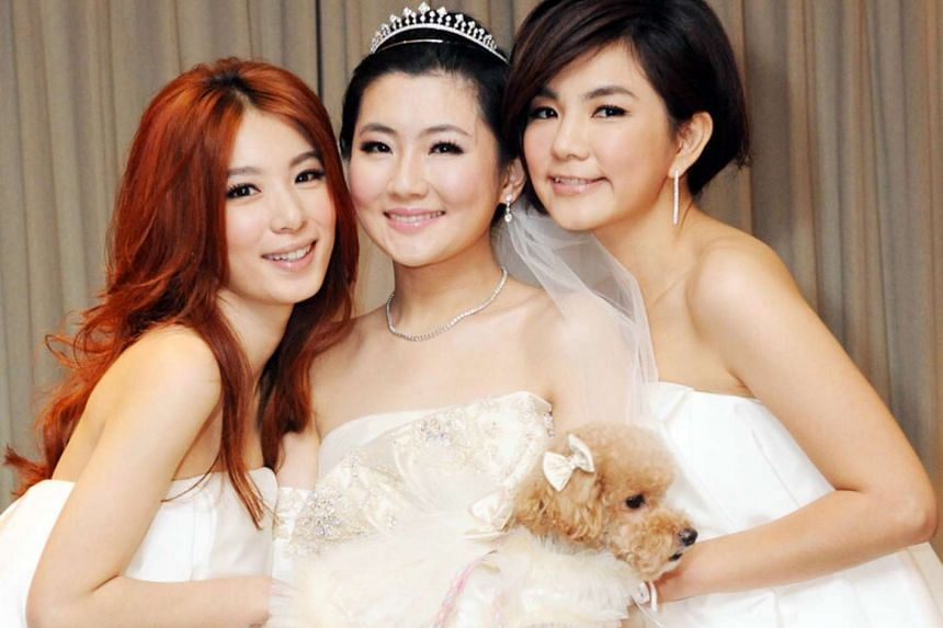 Selina Jen, (centre) singer of popular Taiwanese girl group S.H.E, holding her dog Pinky as she pose with her band mates Hebe Tien (left) and Ella Chen (right) on her wedding day on Oct 31, 2011.