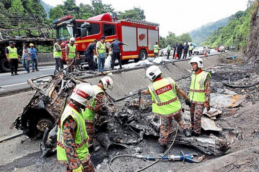 Firemen inspecting the wreckage of the car where the bodies of four accident victims were discovered trapped under a burnt out trailer on the expressway towards Ipoh.