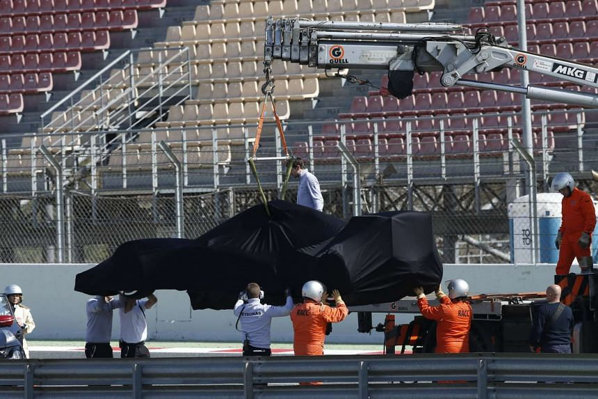 A covered Mercedes F1 car is removed from the track by the mechanics.