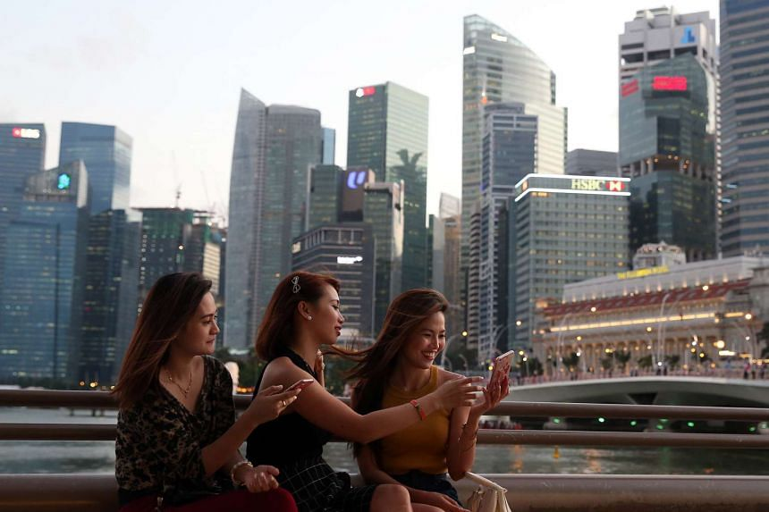 Tourists looking at selfies on their mobile phones outside the Esplanade.