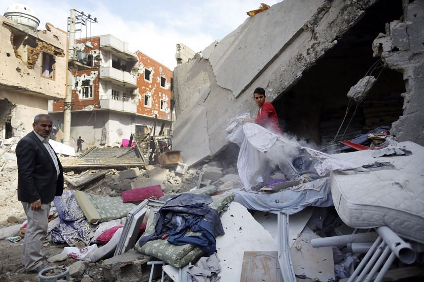 Kurdish people searching through rubble on the street on Thursday, the day after clashes between Turkish special forces and PKK militants broke out in south-east Cizre district in Sirnak, Turkey.