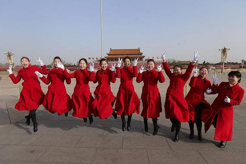 Hostesses all smiles as they execute a jump for the album at the opening of the fourth session of the 12th National People's Congress at Tiananmen Square in Beijing yesterday, attended by about 2,900 delegates.