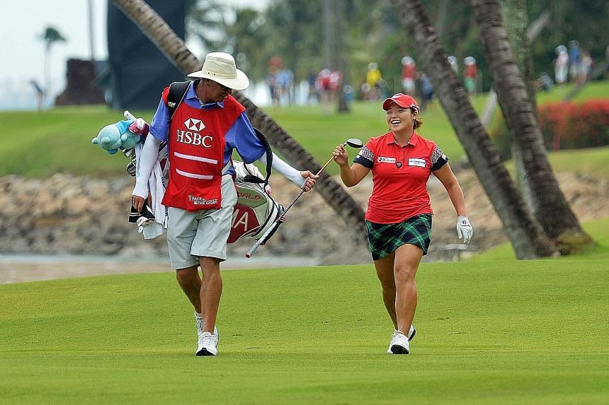 South Korean Jang Ha Na sharing a light-hearted moment with her caddy at the Sentosa Golf Club. After the third round of the HSBC Women's Champions yesterday, the world No. 10 is one stroke ahead of Thailand's Pornanong Phatlum going into today's fin