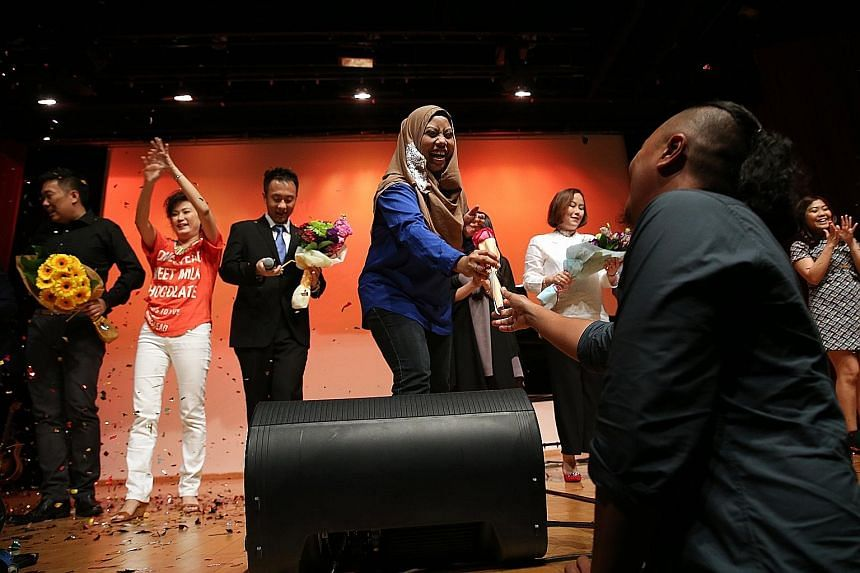 Ms Fazslindah (in blue) receiving a rose from her husband during the grand finale of a charity concert yesterday. The Songbirds - Where Dreams Take Flight matinee is the first large-scale fundraiser by Daughters Of Tomorrow.