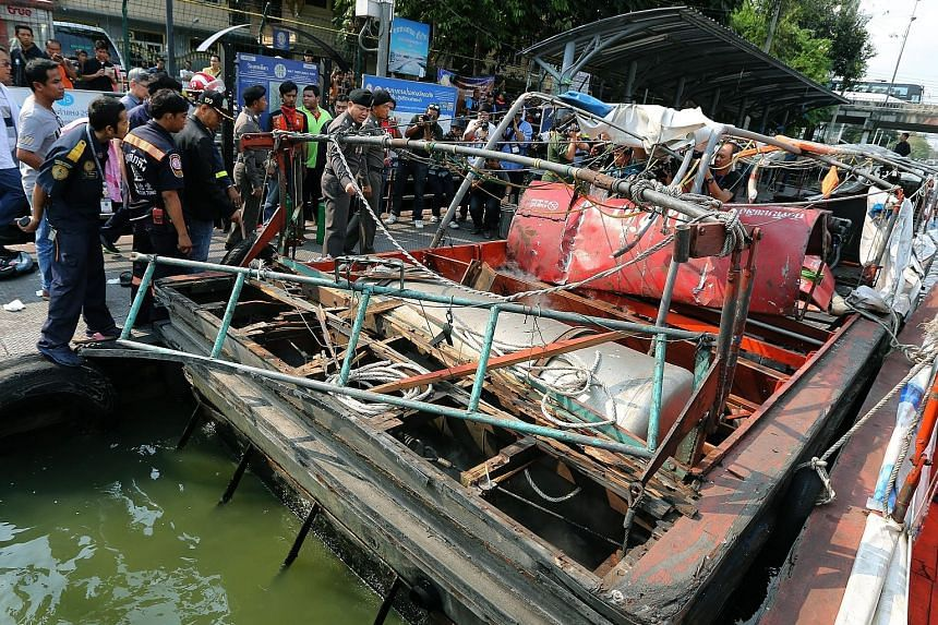 Police officers and officials (left) inspecting what is left of the commuter boat at Wat Thep Leela Pier in Bangkok yesterday. An initial police investigation suggested the explosion (below left) was caused by a fuel leak.