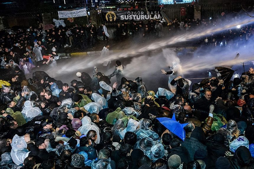 """Turkish riot police using water cannons and tear gas to disperse supporters at the Zaman daily's headquarters in Istanbul just before midnight on Friday. """"The Constitution is suspended,"""" the newspaper, which managed to print its latest issue after th"""