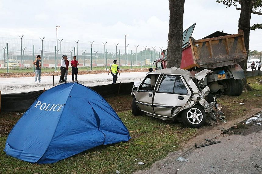 The tipper truck and car in Changi Coast Road after the collision. According to Shin Min Daily News, Mr Zailee's container truck had broken down along the road, and mechanics went down in the car to repair it.