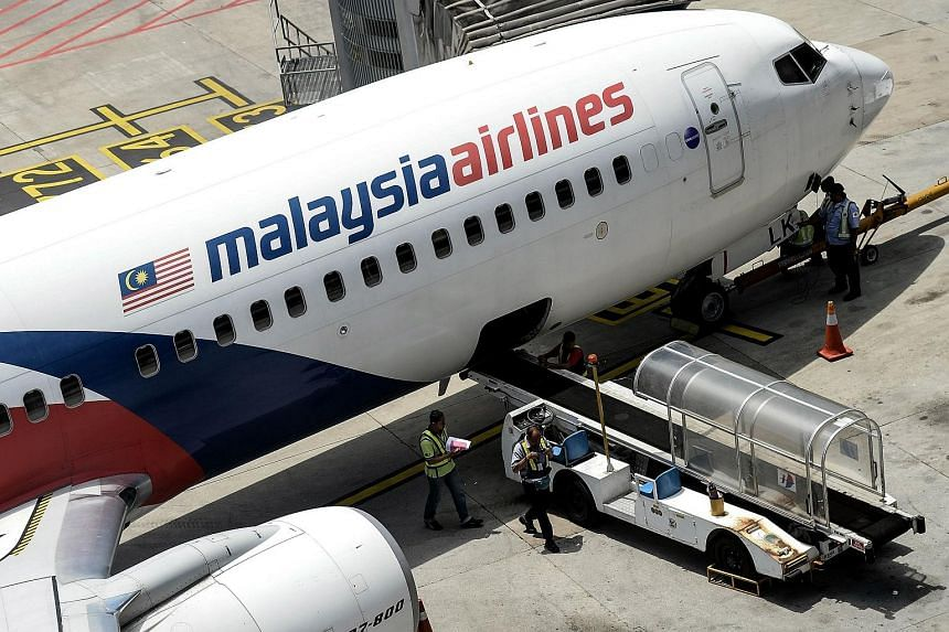 Malaysia Airlines groundstaff walk on the tarmac at Kuala Lumpur International Airport in Sepang, on Feb 25, 2016.