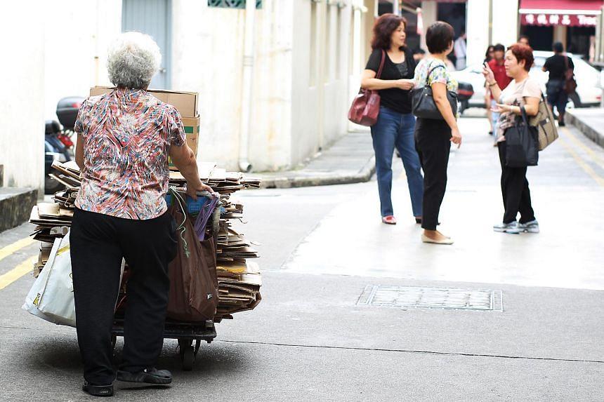 An elderly woman pushing cardboard boxes along the lane of a street.