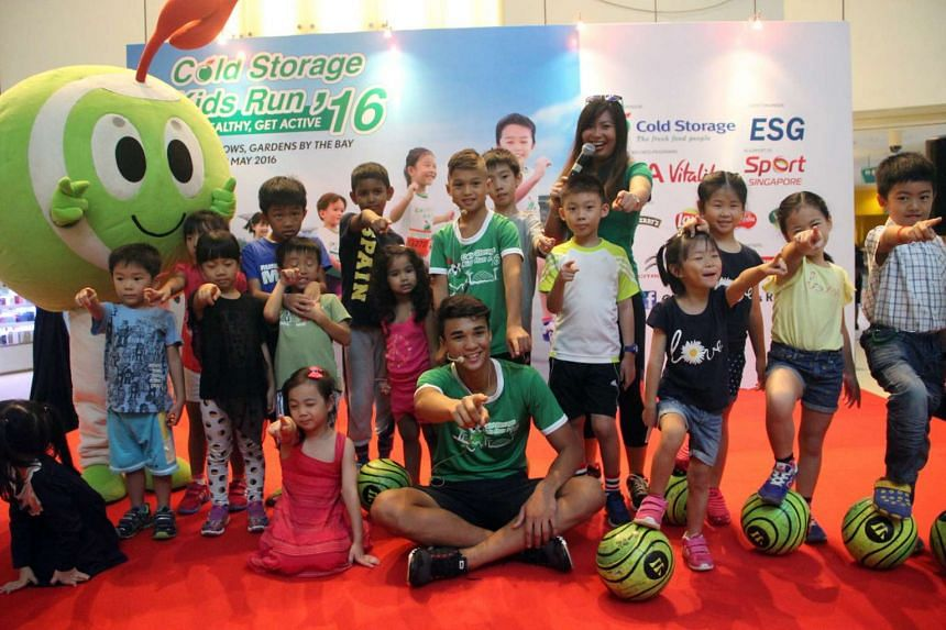 Cold Storage Kids Run ambassador Iryan Fandi (centre) with his older brother Ikhsan and participants of the football clinic, on March 5, 2016.