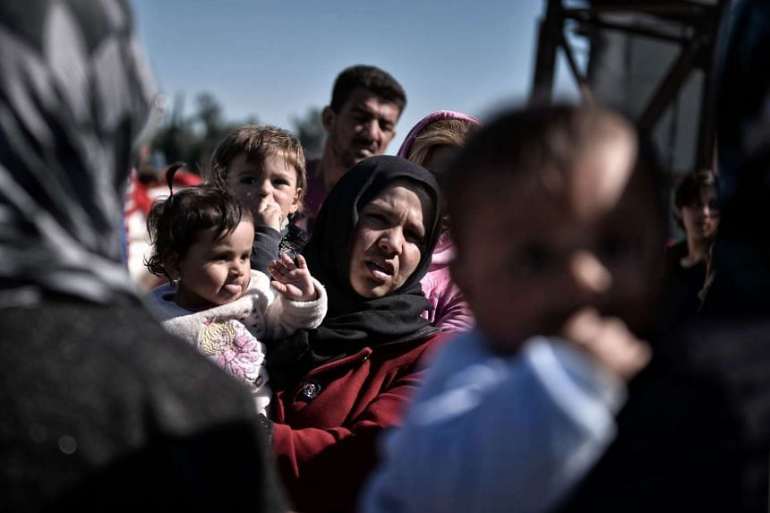 Refugees and migrants look on as aid workers unload supplies at a makeshift camp at the Greek-Macedonian border, on March 5, 2016.