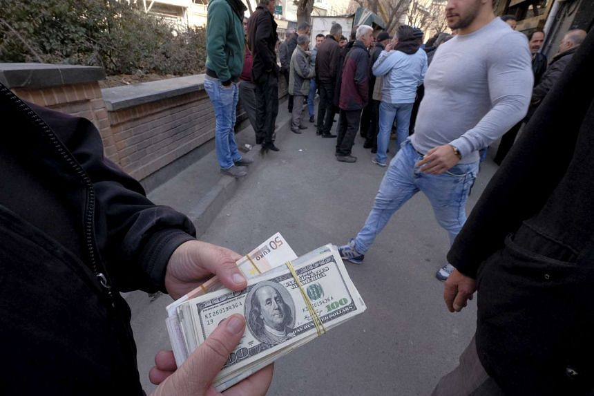 A money changer holds US dollar banknotes as he waits for customers in Teheran's business district.