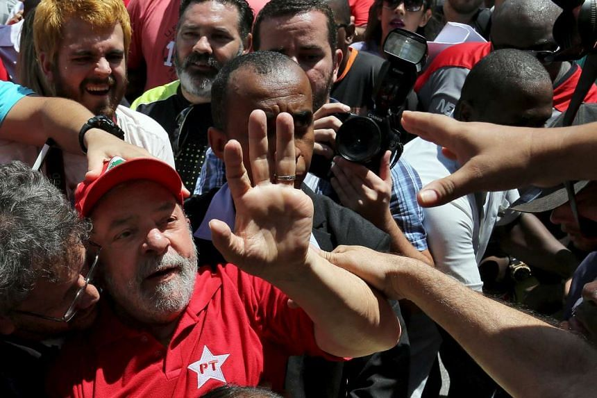 Former Brazilian president Luiz Inacio Lula da Silva is greeted by supporters in front of his home.