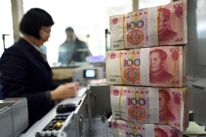 An employee counts 100-yuan notes at a bank in Lianyungang, China.
