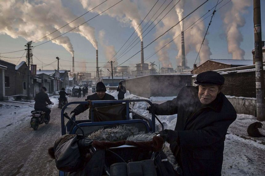 Chinese men pull a tricycle in a neighbourhood next to a coal-fired power plant in Shanxi, China.