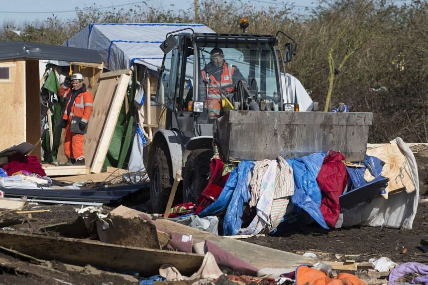 """Workers demolish makeshift shelters in the """"Jungle"""" in Calais, France on March 4, 2016."""