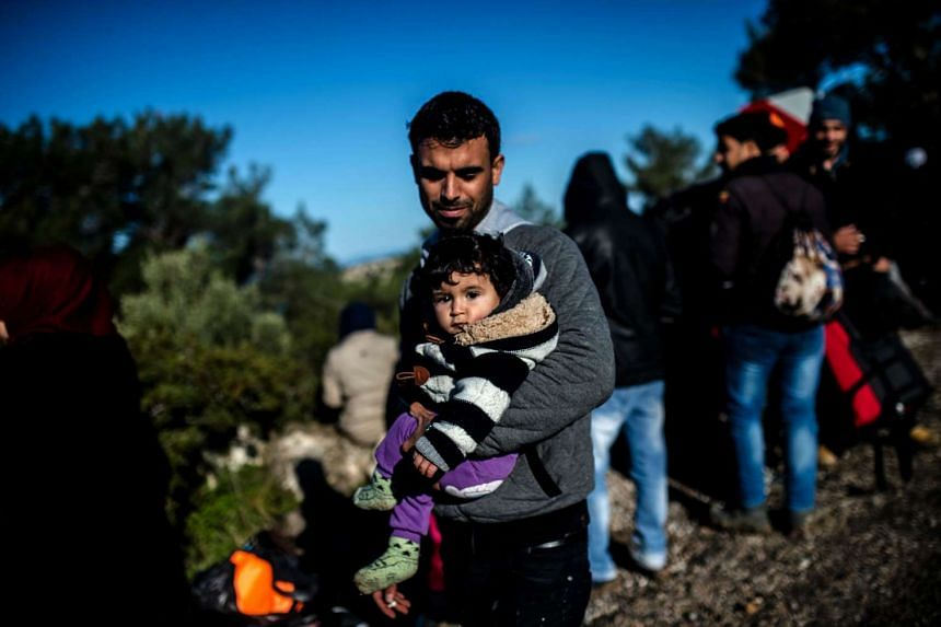 A Syrian father detained by Turkish soldiers holds his child as he tries to reach the Greek island of Lesbos, near the village of Dikili, western Turkey, on March 5, 2016.