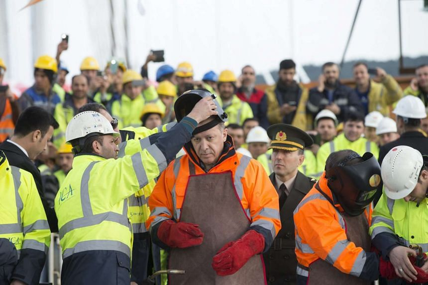 Turkish President Recep Tayyip Erdogan (centre) and Prime Minister Ahmet Davutoglu (2nd from right) preparing for welding the last bridge floor of the Yavuz Sultan Selim Bridge, the Third Bosphorus Bridge during a ceremony in Istanbul, Turkey, on Mar