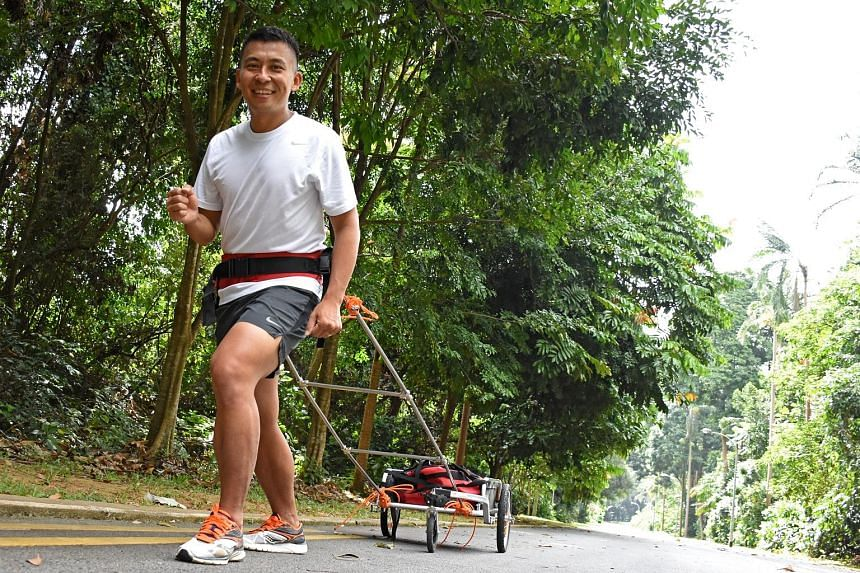 Mr Toh pulls a cart laden with up to 30kg of weight up Bukit Batok Hill as he trains. He remembers going to school without food on some days, and is taking part in the Arctic race to help The Straits Times School Pocket Money Fund.