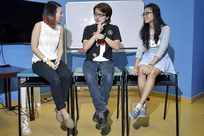 Despite being deaf and juggling heavy schoolwork and CCA commitments, Mr Lau (centre) studied consistently. His former classmates from Millennia Institute, Miss Lena Loke (far left) and Miss Agustin Charisse Grace Esmama, also learnt sign language to