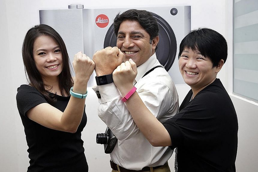 (From left) Finance executive Crystal Lim, 37, managing director Sunil Kaul, 47, and operations manager Sally Yeo, 34, at camera maker Leica, with their Fitbit fitness trackers. The data collected by Fitbit can be used to monitor staff welfare, and t