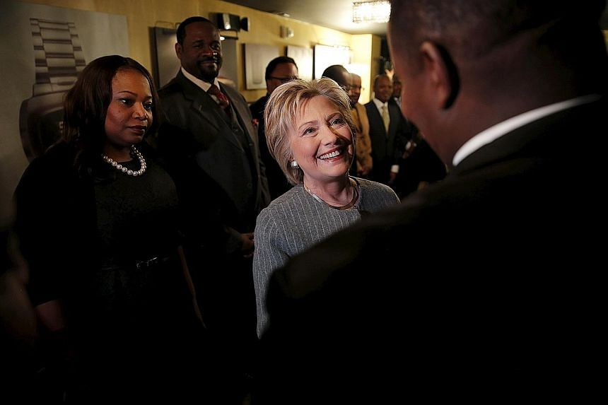 Senator Bernie Sanders (left) arriving for a rally in Warren, Michigan, and Mrs Hillary Clinton (right) meeting African-American ministers in Detroit, Michigan, last Saturday. The next big contest for the Democratic candidates will be tomorrow's prim